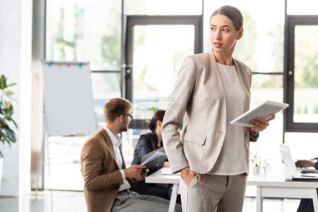 Photo pour Femme d'affaires belle pensive restant avec la main dans la poche et retenant la tablette numérique dans le bureau - image libre de droit
