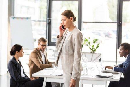 Photo pour Femme d'affaires dans l'usure formelle parlant sur le smartphone dans le bureau - image libre de droit