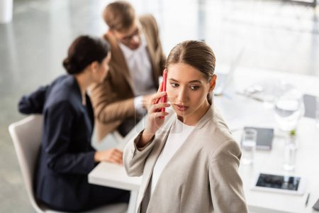 businesswoman in formal wear talking on smartphone in office