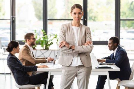 Foto de Vista frontal de la empresaria confiada en ropa formal de pie con los brazos cruzados en la oficina - Imagen libre de derechos