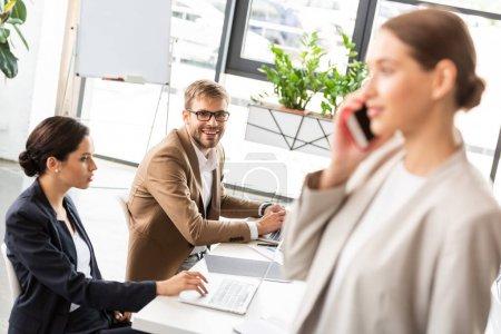 Photo pour Orientation sélective de la femme d'affaires debout près de collègues et de parler sur smartphone dans le bureau - image libre de droit
