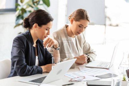 Photo pour Deux femmes d'affaires en tenue formelle à table lors de la conférence en fonction - image libre de droit