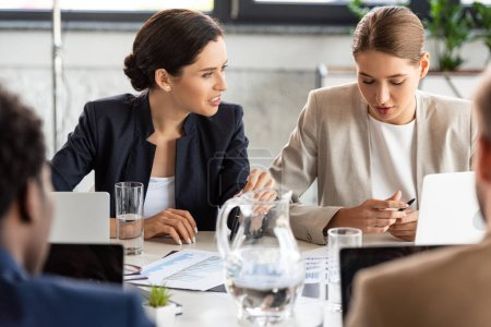Photo pour Vue partielle des gens d'affaires dans l'usure formelle à la table pendant la conférence dans le bureau - image libre de droit