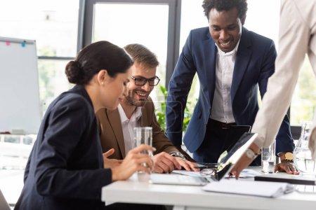 Photo pour Vue partielle des hommes d'affaires multiethniques souriants en tenue de cérémonie à table pendant la conférence au bureau - image libre de droit