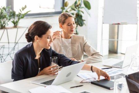 Photo pour Deux femmes d'affaires en tenue formelle à table dans le bureau - image libre de droit