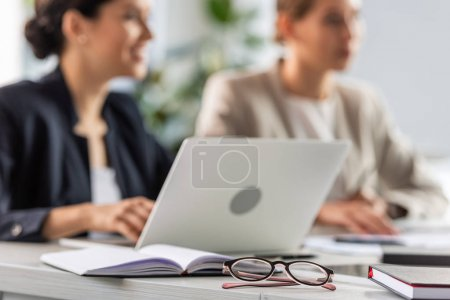 Photo for Selective focus of two businesswomen and laptop at table in office - Royalty Free Image