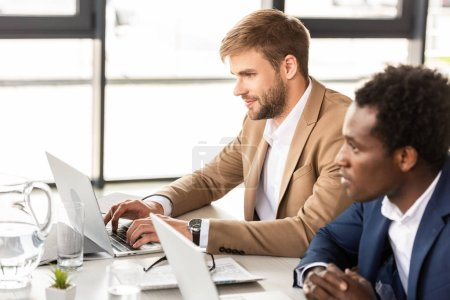 Photo for Two multiethnic businessmen using laptops at table in office - Royalty Free Image