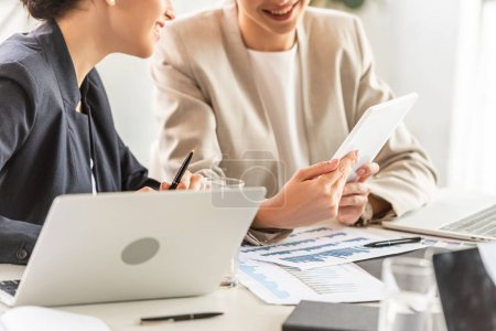 Photo for Partial view of two businesswomen in formal wear at table with laptops and digital tablet in office - Royalty Free Image
