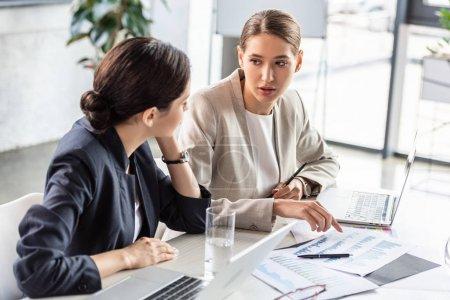 Photo pour Deux femmes d'affaires en tenue formelle à la table en regardant les uns les autres dans le bureau - image libre de droit