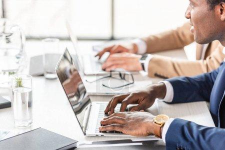 Photo pour Vue partielle de deux hommes d'affaires multiethniques utilisant des ordinateurs portables à la table au bureau - image libre de droit