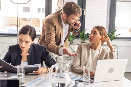 Photo pour Homme d'affaires restant près des collègues dans le bureau et parlant sur le smartphone - image libre de droit
