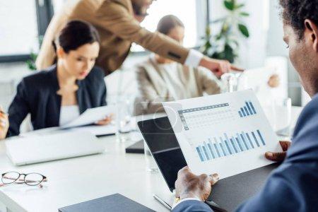 Photo pour Vue partielle des hommes d'affaires multiethniques dans l'usure formelle à la table pendant la conférence dans le bureau - image libre de droit