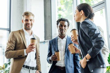 Photo pour Trois collègues multiethniques tenant des tasses jetables de café et souriant au bureau - image libre de droit
