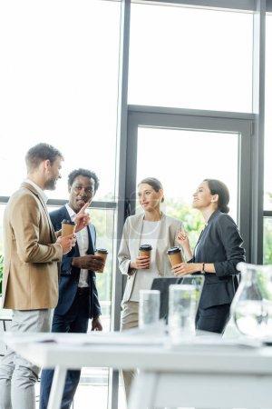 Photo pour Quatre collègues multiethniques tenant des tasses jetables de café et parlant dans le bureau - image libre de droit