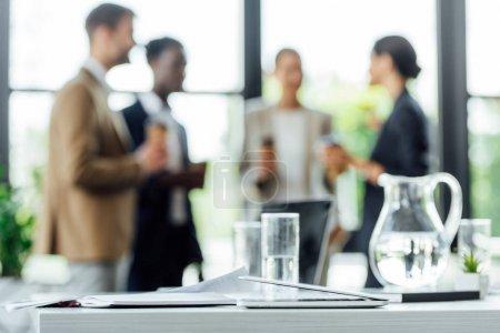 Photo pour Foyer sélectif de quatre collègues multiethniques tenant des tasses jetables de café et souriant dans le bureau - image libre de droit