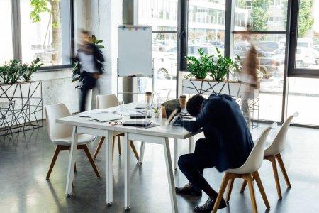 Photo pour Vue arrière de l'homme d'affaires américain africain dormant sur la table dans le bureau - image libre de droit