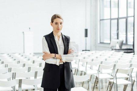 Photo pour Femme attirante dans l'usure formelle avec les bras croisés dans la salle de conférence - image libre de droit