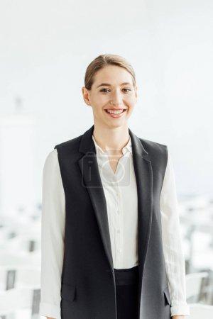 Photo pour Femme d'affaires attirante et heureuse dans l'usure formelle souriante dans la salle de conférence - image libre de droit