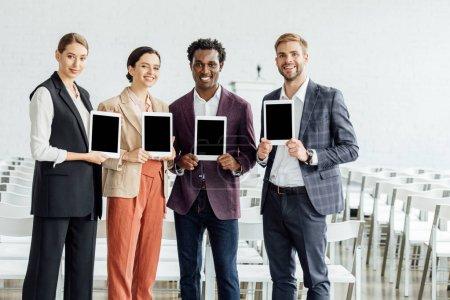 Foto de Cuatro colegas multiétnicos sosteniendo tabletas digitales y sonriendo en la sala de conferencias - Imagen libre de derechos