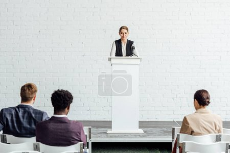 Photo for Attractive businesswoman standing and talking during conference in conference hall - Royalty Free Image