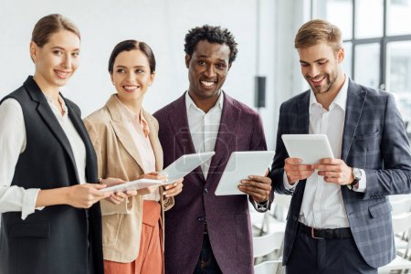 Photo pour Quatre collègues multiethniques tenant des tablettes numériques et parlant dans la salle de conférence - image libre de droit