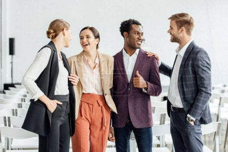 Photo for Four multiethnic colleagues in formal wear talking and smiling in conference hall - Royalty Free Image