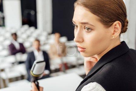 Foto de Enfoque selectivo de atractiva empresaria mirando hacia otro lado durante la conferencia - Imagen libre de derechos