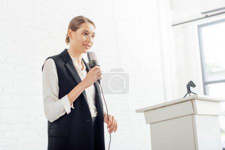 Photo pour Séduisante femme d'affaires tenant microphone et parlant pendant la conférence dans la salle de conférence - image libre de droit