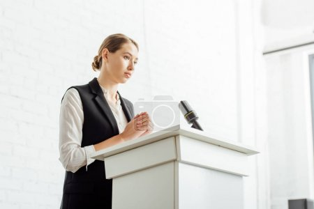 Photo pour Femme d'affaires attirante restant et regardant loin pendant la conférence dans la salle de conférence - image libre de droit