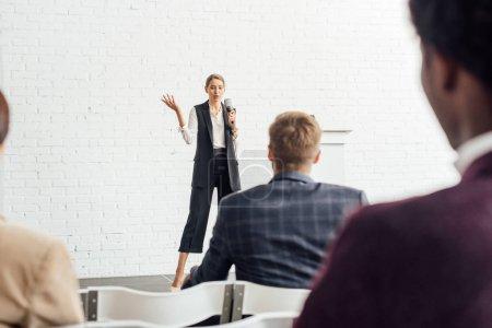 Photo pour Femme d'affaires attirante retenant le microphone et parlant pendant la conférence dans la salle de conférence - image libre de droit