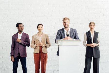 Photo pour Homme d'affaires en tenue de cérémonie parlant pendant la conférence dans la salle de conférence - image libre de droit