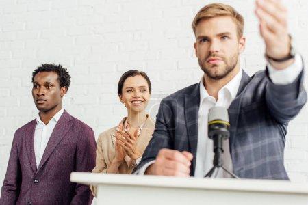Foto de Enfoque selectivo de los empresarios multiétnicos en aplausos formales y sonriendo durante la conferencia - Imagen libre de derechos