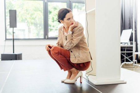 attractive and scared businesswoman in formal wear sitting on floor