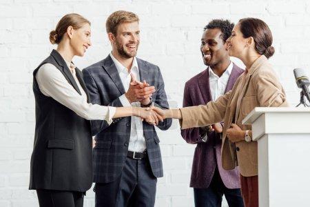 Photo pour Quatre collègues multiethniques en tenue formelle parlant et se serrant la main - image libre de droit