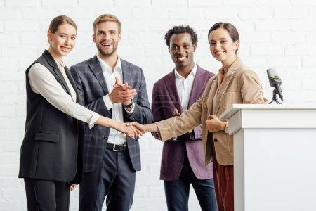 Photo pour Quatre collègues multiethniques en tenue formelle parler et serrer la main dans la salle de conférence - image libre de droit