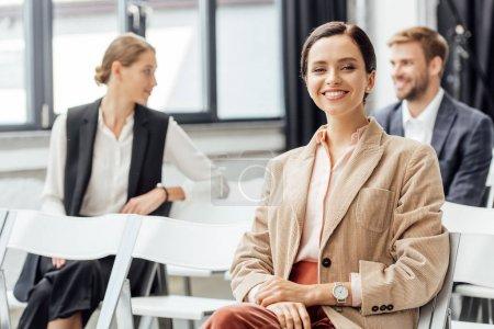 Photo pour Foyer sélectif de la femme attrayante en tenue formelle souriant pendant la conférence - image libre de droit