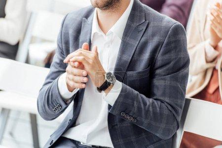 Photo pour Vue recadrée de l'homme d'affaires dans l'applaudissement formel d'usure pendant la conférence - image libre de droit