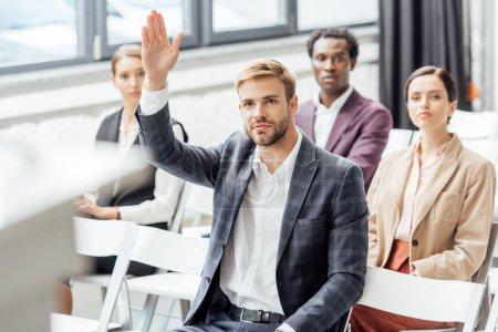 Photo pour Orientation sélective de l'homme d'affaires soulevant la main pendant la conférence dans la salle de conférence - image libre de droit