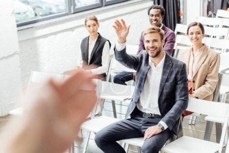 Foto de Enfoque selectivo del hombre de negocios levantando la mano y sonriendo durante la conferencia - Imagen libre de derechos