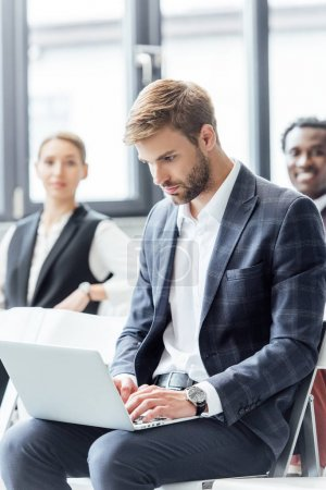 Photo pour Focus sélectif de l'homme d'affaires dans l'usure formelle à l'aide d'ordinateur portable pendant la conférence - image libre de droit