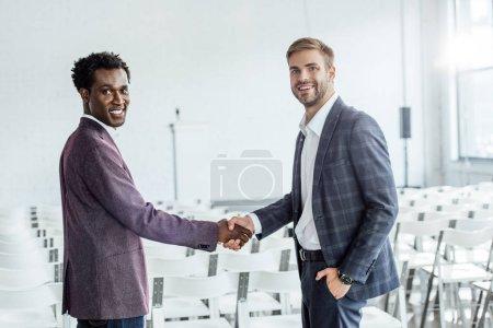 Photo pour Deux collègues multiethniques en tenue formelle se serrant la main dans la salle de conférence - image libre de droit