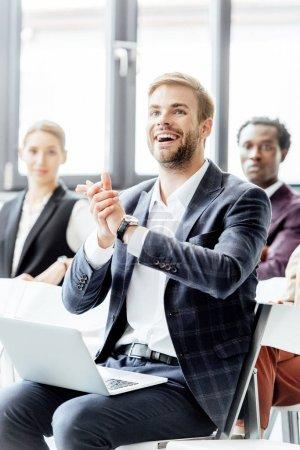 Photo pour Foyer sélectif de l'homme d'affaires dans l'usure formelle tenant l'ordinateur portable et applaudissant pendant la conférence - image libre de droit