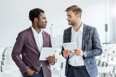 Foto de Dos colegas multiétnicos en uso formal utilizando tabletas digitales en la sala de conferencias - Imagen libre de derechos