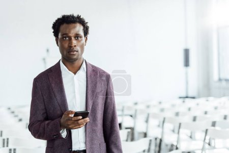 Photo for African american businessman in formal wear holding smartphone in conference hall - Royalty Free Image