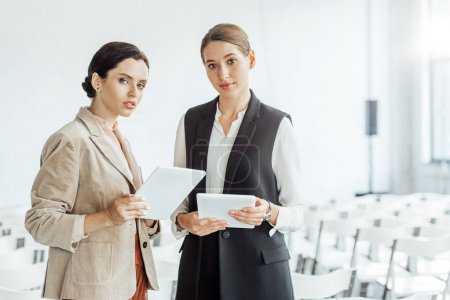 Photo for Two attractive colleagues in formal wear holding digital tablets in conference hall - Royalty Free Image