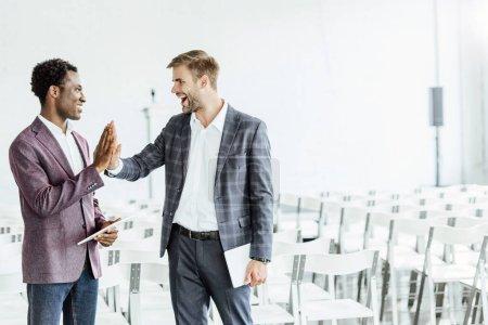 Photo pour Deux collègues multiethniques en tenue formelle tenant des tablettes numériques dans la salle de conférence - image libre de droit