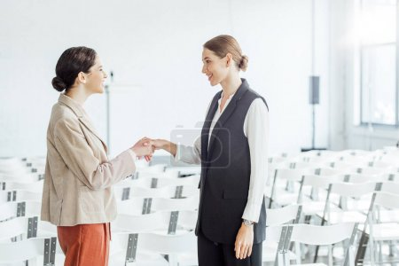 Photo for Two attractive colleagues in formal wear shaking hands in conference hall - Royalty Free Image