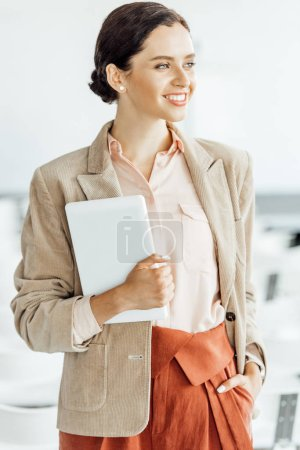 attractive businesswoman in formal wear smiling and holding digital tablet