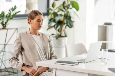 attractive businesswoman in formal wear sitting and looking at laptop