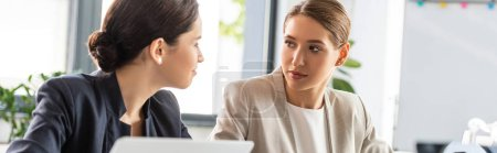 Photo for Panoramic shot of two businesswomen in formal wear talking in office - Royalty Free Image